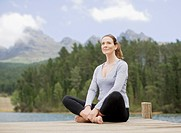 Woman practicing yoga on pier by lake