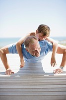 Father doing push_ups with son on his back