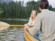 Couple rowing canoe on lake