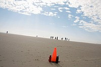people gather to play soccer on the beach with orange boundary cone