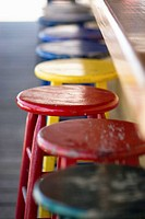 primary colored stools await bar patrons at an outside beach bar