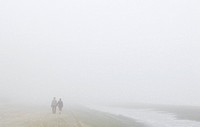 Walking in fog. Man and woman strolling hand_in_hand along a beach in thick fog. Photographed at Myrtle Beach, South Carolina, USA, in December.