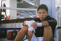 Japanese boxer sitting in Boxing ring