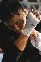 Japanese boxer tying bandage on his knuckles before fight