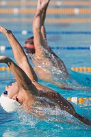 Swimmers with arms raised doing backstroke swimming