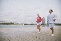 Young couple jogging on wharf