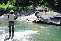 Man with straw hat standing on stone and fishing