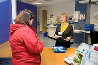 Hospital pharmacy. Patient left collecting and discussing her prescription with a pharmacist at the outpatients pharmacy of a hospital. Photographed a...