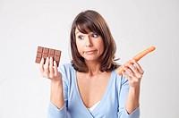 Eine junge Frau haelt in einer Hand eine Moehre, in der anderen eine Tafel Schokolade, a young woman holding a carrot in one hand and a bar of chocola...