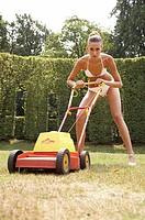 Junge Frau im Bikini mit Rasenmaeher im Garten, young woman wearing a bikini with a lawnmower in the garden