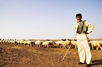 Portrait of a shepherd standing with arms akimbo, Jaisalmer, Rajasthan, India