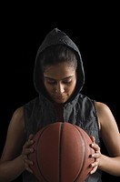 Close_up of a young woman holding a basketball