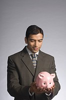 Businessman holding a piggy bank