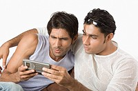 Two friends text messaging on a mobile phone