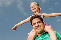 Low angle view of girl sitting on her father's shoulders