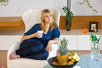 Woman sitting in armchair and holding coffee cup