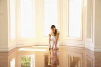 Hispanic woman measuring wooden floor