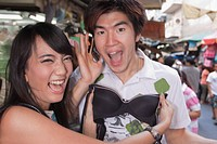 Asian woman holding up bra to boyfriend