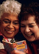 Senior women sharing funny book together