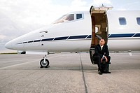 Businessman sitting on a private airplane's steps