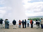 A group of people standing in front of the Strokkur Geyser, Iceland