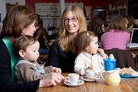 Two mother´s in a cafe with children sitting on their laps