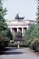 Person standing in park behind Brandenburg Gate, Berlin, Germany