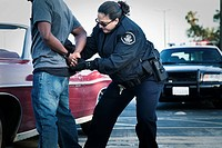 Hispanic policewoman handcuffing man
