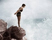 Female swimmer on rock above crashing surf Old Visuals