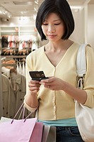 Filipino woman text messaging in clothing store