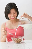 Filipino woman pouring milk over cereal