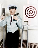 Young man looking at a mirror and aiming at a dartboard with a handgun Old Visuals