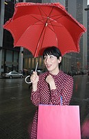 Young woman standing on street holding an umbrella and shopping bags, New York City