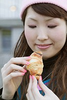 Young woman holding chocolate croissant