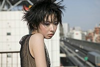 Young woman standing on rooftop and looking down, Tokyo, Japan