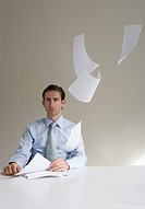 Businessman sitting at desk with paper floating in mid_air