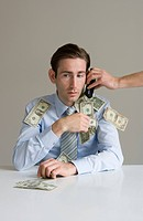 Businessman using telephone covered in money