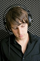 Young man wearing headphones in recording studio