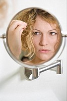Woman looking anxious in the mirror