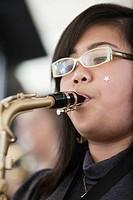 Teenage girl playing saxophone