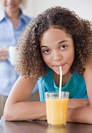 Mixed race girl drinking orange juice with straw