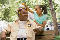 African granddaughter decorating grandfather´s head with flowers