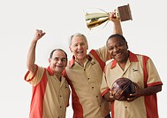 Men in team uniforms holding bowling ball and trophy