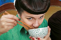 Close up of young rockabilly woman holding soup bowl and chopsticks