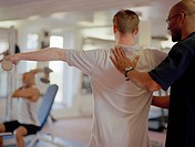 Exercise instructor helping man in gym