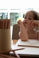 Young girl sitting at a table with a sketch pad and colored pencils
