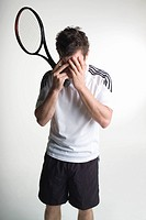 A tennis player covering his face with his hands