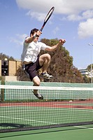 A tennis player leaping over a tennis net