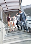 Businessmen and businesswoman walking down stairs
