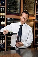 A barman pouring a glass of red wine